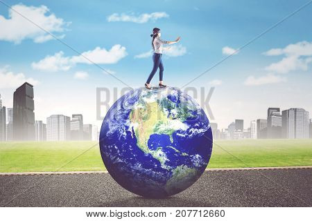 Young blindfolded businesswoman walks on Earth planet while finding a way. Elements of this image furnished by NASA