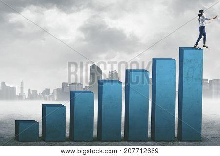 Young blindfolded businesswoman stepping on the top graph while finding a way. Shot outdoors