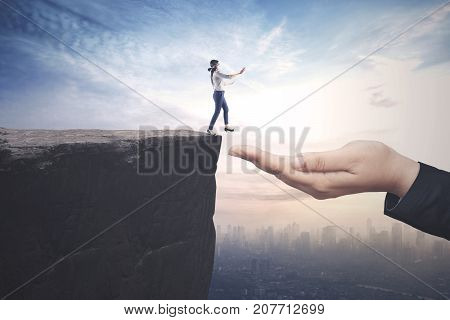 Helping hands concept. Young blindfolded businesswoman walking on the cliff towards a helping hand
