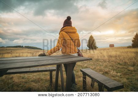 Girl on a meadow / mountain field looking at the distance.