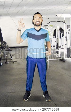 African man measuring his waistline with measure tape and showing OK sign in the fitness center
