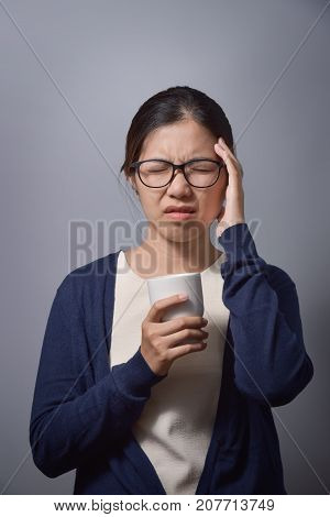 Tired Asian glasses woman having headache and holding cup of hot coffee. Copy space. Migraine from Overtime working. Diseases Illness concept.