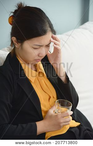 Tired Asian glasses business woman holding glass of water and having headache. Migraine from Overtime working. Diseases Illness concept.