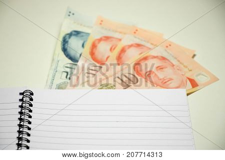 Blank note book with Singapore dollar on white desk background