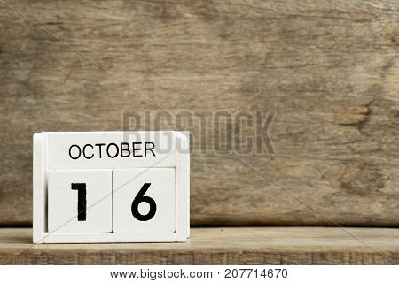 White block calendar present date 16 and month October on wood background