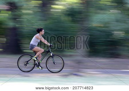 Young Woman Riding A Bike In The Park