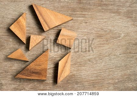 Straggled tangram puzzle wait to complete the shape on wood background