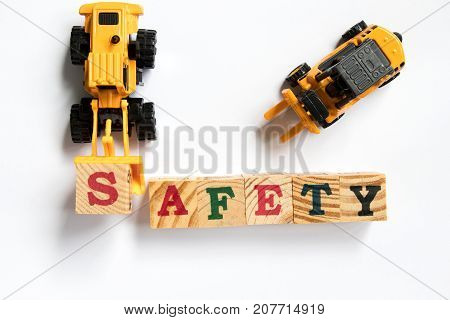 Toy plastic bulldozer hold toy block letter s to fulfill word safety with foklift on white background