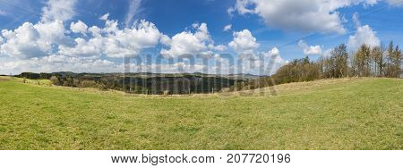 Panoramic view over a meadow and hills of the south Eifel landscape with deep blue sky near Daun Germany. poster