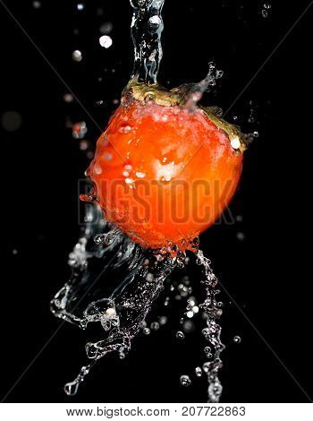 persimmon in water on a black background