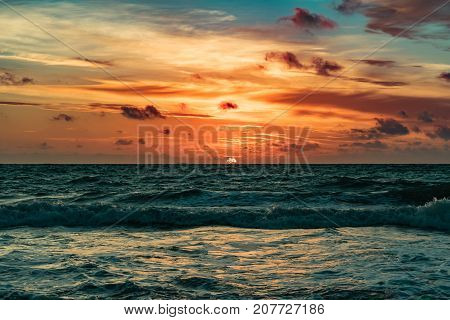orange sun rising on the horizon on a windy morning with wavy green waters