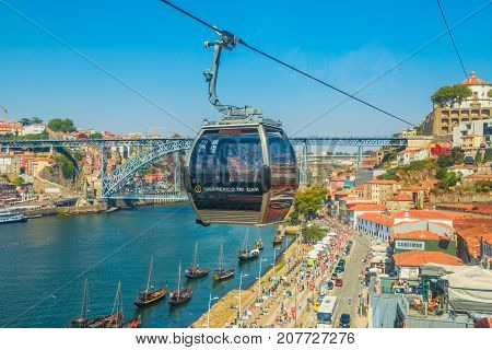 Porto, Portugal - August 13, 2017: Aerial view of Dom Luis I Bridge on Douro River, Monastery of Serra do Pilar and Riberira skyline from Teleferico de Gaia, a cable car in Vila Nova de Gaia.