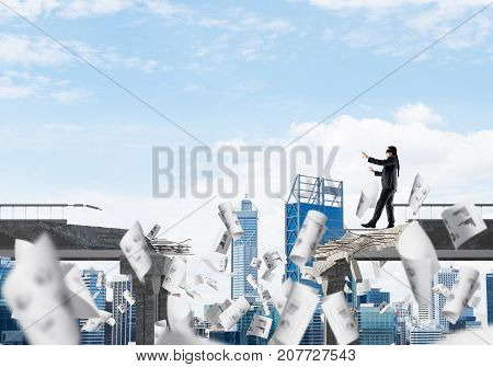 Businessman walking blindfolded among flying papers on concrete bridge with huge gap as symbol of hidden threats and risks. Cityscape view on background. 3D rendering.