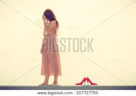 Hobby idyllic aspects of femininity concept. Woman walking on jetty without shoes wearing beautiful long light pink dress.