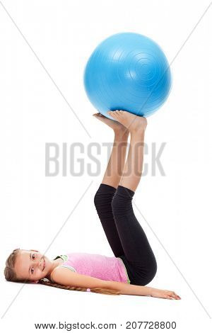 Young girl doing strength and balance gymnastic exercises - using a large rubber gym ball, isolated