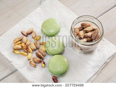 Peeled and unpeeled pistachio nuts and pistachio flavored macarons presented on a white napkin presented