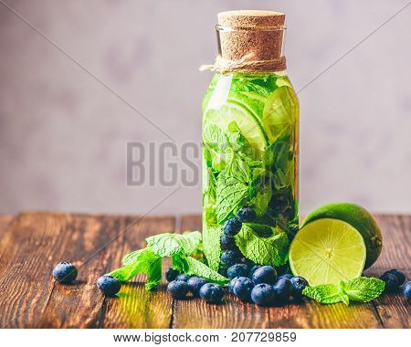 Infused Water in Bottle with Lime Mint and Blueberry and Ingredients on Table. Copy Space on the Left.