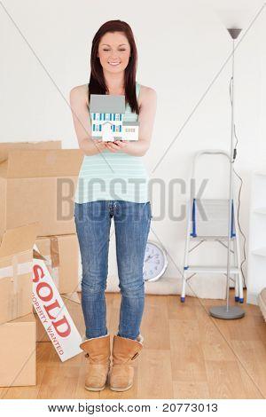Schöne Rothaarige Frau hält eine Miniatur Haus stehen auf dem Boden zu Hause