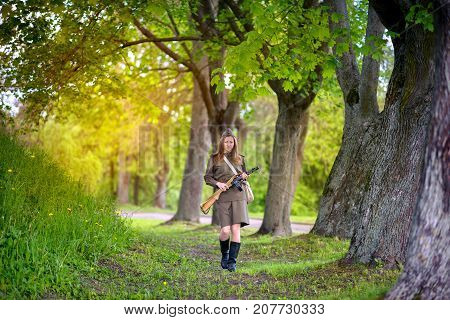 woman the defender costs with automatic machine in the wood at sunset