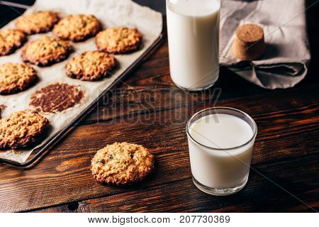 Homemade Oatmeal Cookies with Raisins and Glass of Milk for Breakfast. Some Cookies on Parchment Paper with Bottle on Backdrop.