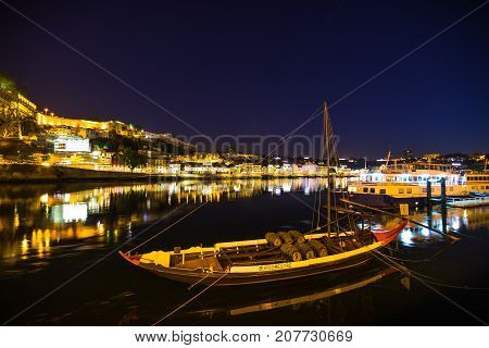 Porto, Portugal - August 10, 2017: a traditional Rabelo boat, used for transportation of port wine from Douro Valley, to wine cellars in Vila Nova de Gaia. Ribeira waterfront illuminated by night.