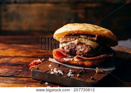 The Casanova Burger on Cutting Board. Cheeseburger with Beef Patty Wisconsin Swiss Cheese Ham Sauteed Mushrooms Dijon Mustard Mayonnaise and Potato Roll. Wooden Background and Copy Space.