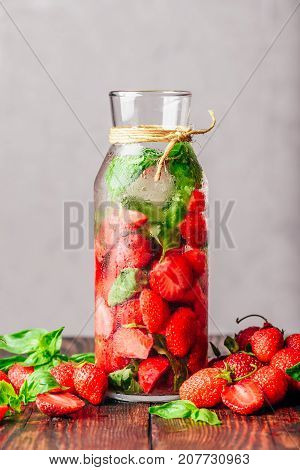 Bottle of Water Infused with Fresh Strawberry and Basil Leaves. Scattered Ingredients on Wooden Table. Vertical Orientation and Copy Space.