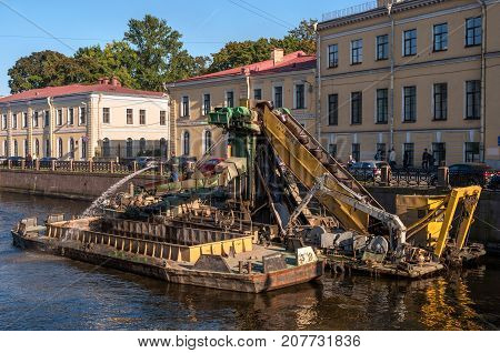 St. Petersburg, Russia - September 24, 2017: Work to deepen the bottom in the channel of the urban river Moika. Dredging machine raises the river bed.
