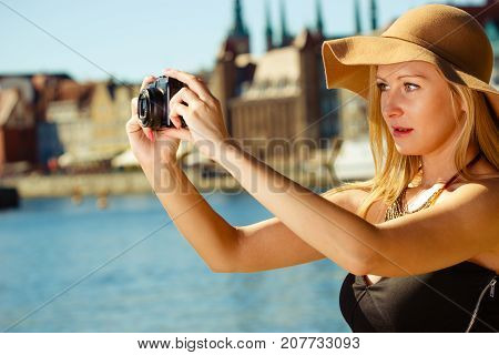 Tourism artistic elegant fashion. Woman in elegant outfit and sun hat taking pictures.