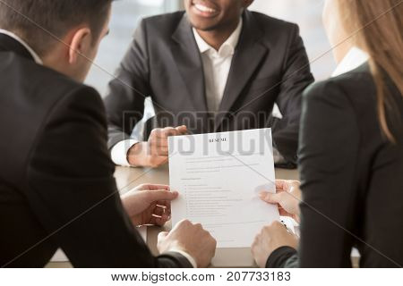HR managers analyzing resume, asking afro american applicant about skills, actual work experience. Recruitment agency hiring specialist, conducting interview with candidate for vacancy. Close up view