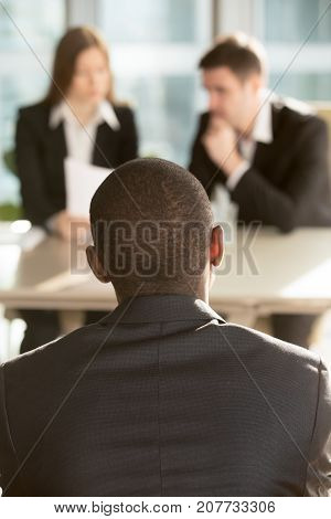 African american male job candidate waiting for hiring decision on job interview, caucasian employers reading resume on background. Millennial black man interested in vacancy searching his first job