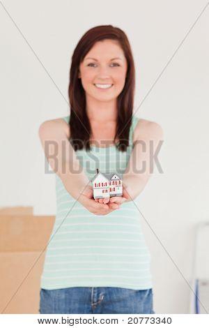 Wunderschöne Rothaarige Frauen halten ein Miniatur-Haus stehen auf dem Boden zu Hause