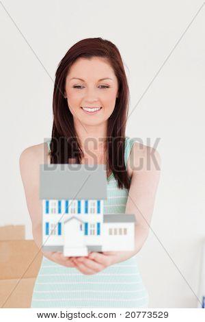 Gut aussehende Rothaarige Frau hält ein Miniatur-Haus stehen auf dem Boden zu Hause