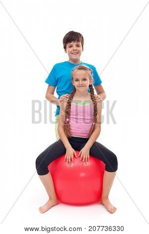Kids relaxing after workout - girl sitting on large rubber gymnastic ball, isolated