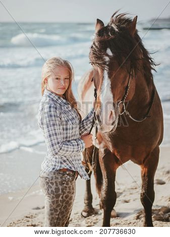 Beautiful fair-haired girl in armor with a horse on the background of the sea. blonde woman near black horse at sea beach. Beautiful woman wearing casual clothing enjoying sunrise morning