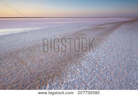 Brine and salt of a pink lake, colored by microalgae Dunaliella salina at sunset