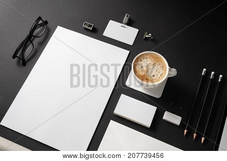 Photo of blank stationery set on black paper background. Responsive design mockup. ID template. Top view.