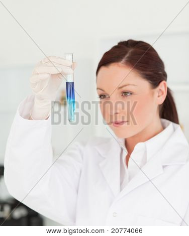 Beautiful red-haired scientist looking at a test tube in a lab