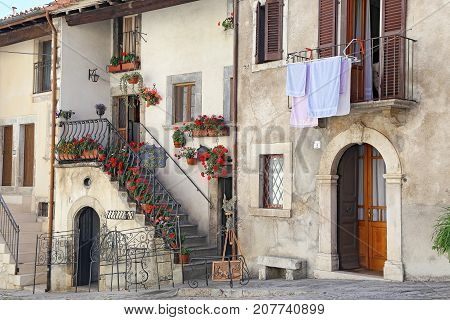 PESCOCOSTANZO ITALY - AUGUST 18 2015: Nice facades in steep alley. The mountain village - about 1400 m above sea - Pescocostanzo in the region of Abruzzo Italy
