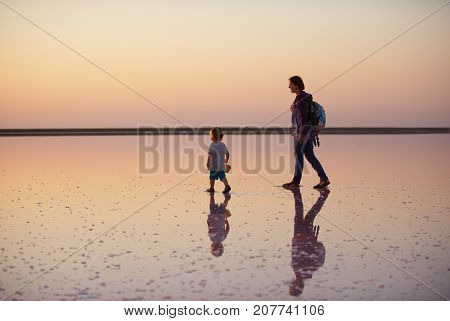 Mother and child walking on a salt and brine of a pink lake, colored by microalgae Dunaliella salina at sunset