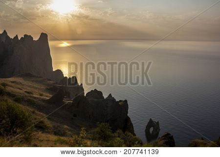 Golden or Devil's  Gate at dawn, a famous rock formations near the extinct volcano Karadag Mountain in KaraDag reserve in Crimea A huge rock with a big hole.