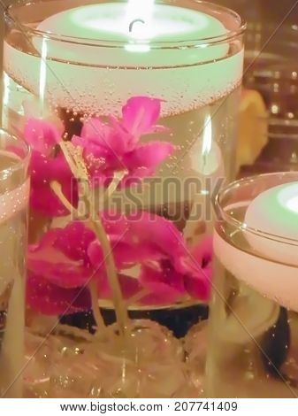 This votive is floating in a glass with clear beads and flowers filled with water