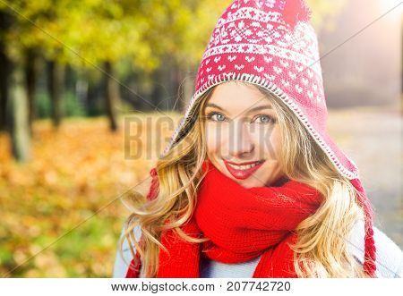 Happy Woman in Beanie Hat on Autumn Background in Sunny Day. Smiling Blonde Girl Portrait. Beautiful Young Female. Toned Photo with Copy Space.