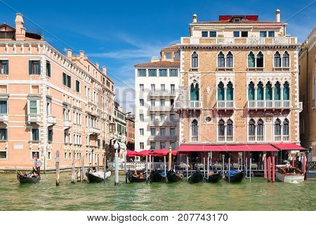 VENICE,ITALY - JULY 25,2017 : Gondolas and luxury hotel on an old palace by the Grand Canal in Venice