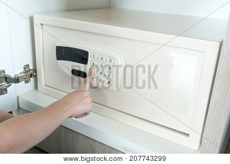 Kid finger inserting password on electronic padlock of metal steel safe box.