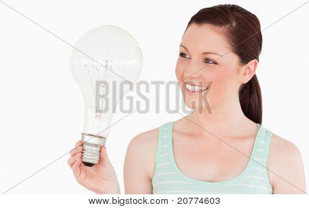 Hübsche rothaarige Frau hält eine Glühbirne stehen auf einem weißen Hintergrund
