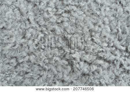 Light gray artificial curly fur texture. Macro. Closeup