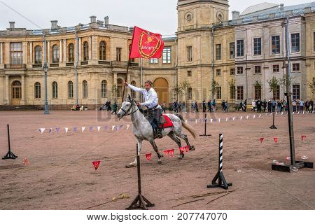 Gatchina St. Petersburg Russia - September 30 2017: Horse show of Cossacks on the parade ground of the Gatchina Palace. A Cossack in a white shirt jumps with a red flag.