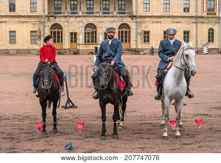 Gatchina St. Petersburg Russia - September 30 2017: Horse show of Cossacks on the parade ground of the Gatchina Palace. Three Cossack riders stand in front of the audience.