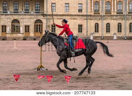 Gatchina St. Petersburg Russia - September 30 2017: Horse show of Cossacks on the parade ground of the Gatchina Palace. The young Cossack performs tricks on the horse.